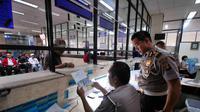 Petugas memberi penjelasan pada wajib pajak di Samsat Jakarta Pusat, Kamis (11/12/2014). (Liputan6.com/Johan Tallo)