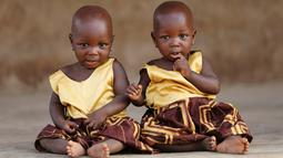 """Si kembar identik, Taiwo Adejare dan Kehinde Adejare berpose untuk sebuah foto di Igbo Ora, Negara Bagian Oyo, Nigeria pada 4 April 2019. Saking banyaknya anak kembar yang dilahirkan, Igbo Ora dijuluki sebagai """"ibu kota kembar dunia"""". (REUTERS/Afolabi Sotunde)"""