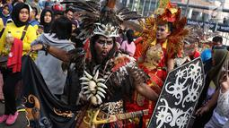 Kelompok seni budaya Kalimantan Selatan berpawai mengenakan pakaian adat saat pelaksanaan car free day di Jakarta, Minggu (1/7). Pawai tersebut diadakan untuk mengenalkan budaya Kalimantan Selatan kepada masyarakat. (Liputan6.com/Immanuel Antonius)
