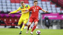 Pemain Bayern Munchen, Joshua Kimmich, berebut bola dengan pemain FC Koln, Ondrej Duda, pada laga Bundesliga di Stadion Allianz, Minggu (27/2/2021). Bayern menang dengan skor 5-1. (AP/Andreas Schaad)
