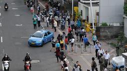 Pekerja berjalan kaki saat pulang kantor di Jalan Sudirman menuju Bendungan Hilir, Jakarta, Rabu, (22/4/2015). Tak adanya bus yang melintas karena adanya pengalihan arus untuk KAA membuat mereka terpaksa jalan kaki. (Liputan6.com/Johan Tallo)