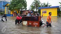 Penyedia jasa gerobak mengangkut warga dan motornya untuk menyeberangi banjir di Jalan Gunung Sahari, Jakarta Pusat, Selasa (21/2). Hujan deras yang mengguyur sejak Selasa dini hari membuat sebagian wilayah di Jakarta banjir. (Liputan6.com/Faizal Fanani)