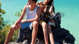 Selain bermain di laut, Christian dan Titi juga berfoto di tempat-tempat indah lainnya. Seperti ketika mereka berfoto di atas batu Termanu yang memperlihatkan indahnya perpaduan warna hijau dan birunya air laut dengan hutan. (Liputan6.com/titi_kamall)