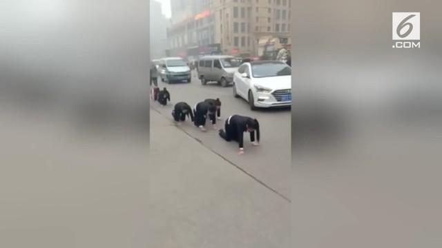 Sekelompok karyawan dihukum dengan cara merangkak di pinggir jalan kota Zaozhuang, China. Hukuman ini karena para karyawan gagal memenuhi target yang telah ditentukan.