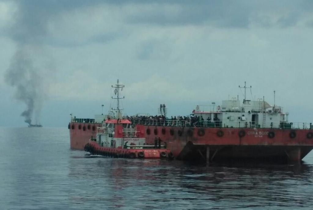 Asap yang membakar KM Dharma Kencana II terlihat mengepul ketika Kapal SAR Sadewa mendekati. (foto : Liputan6.com/Basarnas/edhie prayitno ige)