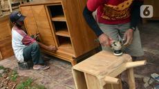 Pekerja menghaluskan furnitur atau perlengkapan rumah berbahan kayu dari Jepara di Ciputat, Tangerang Selatan, Selasa (14/9/2021). Pedagang di tempat tersebut mengakui selama PPKM ini daya beli masyarakat terhadap furnitur meningkat. (Liputan6.com/Johan Tallo)