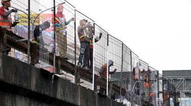 Pekerja melakukan pengecatan pagar pembatas jalan tol di Tomang, Kebun Jeruk, Jakarta, Rabu (30/5). Pengecatan tersebut dilakukan sebagai upaya perawatan dan mengatasi pagar yang sudah karat. (Liputan6.com/Johan Tallo)