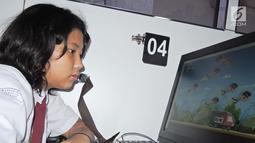 Seorang siswi SD bermain game antikorupsi saat menaiki Bus KPK di Balai Kota Semarang, Jawa Tengah, Sabtu (13/10). Selain melalui game, KPK juga menanamkan antikorupsi melalui dongeng dan film. (Liputan6.com/Gholib)