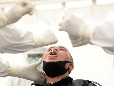 Petugas medis mengambil sempel lendir salah satu peserta test SWAB massal gratis di halaman Dinas Kesehatan Tangeramg Selatan, Banten, Minggu (30/8/2020). Test Swab gratis tersebut diikuti 750 orang untuk pencegahaan penyebaran Covid-19. (merdeka.com/Dwi Narwoko)