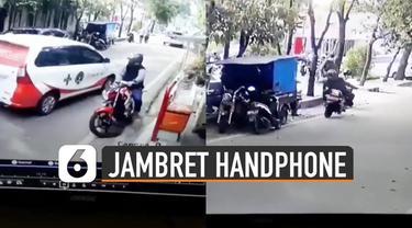Video CCTV memperlihatkan seorang pria menggunakan sepeda motor menjambret handphone di pinggir jalan.
