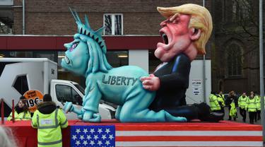 Sebuah patung berbentuk menyerupai Patung Liberty dan Presiden AS ikut dalam karnaval tradisional 'Rose Monday' di Dusseldorf, Jerman Barat, Senin (27/2). Karnaval 'Rose Monday' berisi sindiran satir para pemimpin dunia. (AFP PHOTO / Patrik STOLLARZ)