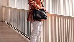 Ciki juga menyukai outfit dengan warna cerah seperti kemeja orange yang dipadukan dengan hijab krem, tas hitam, celana dan heels berwarna putih. (Liputan6.com/IG/@citraciki)