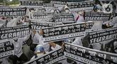 Massa calon pekerja migran Indonesia membawa poster memadati badan jalan Gatot Subroto, berunjuk rasa di depan kompleks Kemenaker, Jakarta, Senin (18/10/2021). Aksi dilakukan untuk menuntut kejelasan status penempatan mereka. (Liputan6.com/Faizal Fanani)