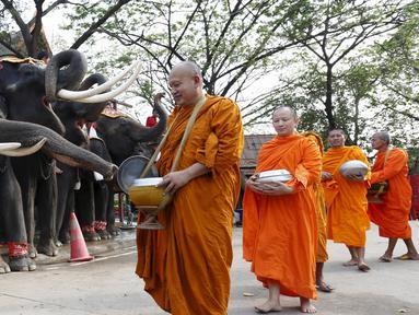 Sejumlah Biksu Buddha memberi pemberkatan kepada gajah saat perayaan Hari Gajah Nasional di kota bersejarah, Thailand, (3/11). Gajah merupakan ikon di negara Thailand. (REUTERS / Chaiwat Subprasom)