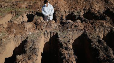 Seorang pekerja beristirahat saat menggali kuburan di pemakaman San Vicente di Cordoba, Argentina, 14 April 2020. Pemerintah kota di provinsi Argentina tengah, Cordoba telah menggali sekitar 250 kuburan untuk mengantisipasi peningkatan korban jiwa dari pandemi Covid-19. (AP/Nicolas Aguilera)