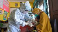 Perawat mengenakan alat pelindung diri saat menyuntikkan vaksin campak kepada seorang anak di Hari Perawat Internasional di Palu, Indonesia, Selasa (12/5/2020). Hari Perawat Internasional diperingati setiap tanggal 12 Mei yang bertepatan dengan kelahiran Florence Nightingale. (MUHAMMAD RIFKI/AFP)