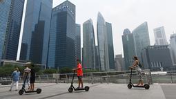 Orang-orang menggunakan skuter skate di sepanjang Marina Bay ketika bangunan diselimuti kabut asap di Singapura (13/9/2019). Titik api di hutan hujan Indonesia telah melonjak tajam, data satelit menunjukkan pada 12 September, menyebarkan kabut asap di Asia Tenggara. (AFP Photo/Roslan Rahman)