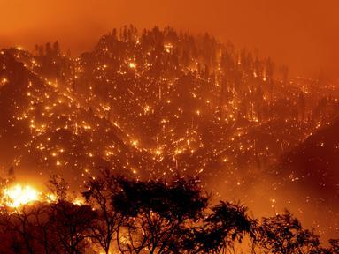 Dalam foto eksposur panjang ini menunjukkan bara api menyala pada lereng bukit saat Dixie Fire membakar dekat Milford di Lassen County, California, Amerika Serikat, Selasa (17/8/2021). Kebakaran hutan mengancam untuk menyebarkan ke beberapa wilayah di California utara. (AP Photo/Noah Berger)