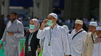 Umat Muslim mengenakan masker di Masjidil Haram, kota suci Makkah, Kamis (27/2/2020). Suasana Masjidil Haram berjalan sebagaimana biasanya pascapengumuman Pemerintah Arab Saudi melarang sementara jemaah umrah ke Tanah Suci terkait pencegahan penyebaran virus korona. (Abdulghani BASHEER/AFP)