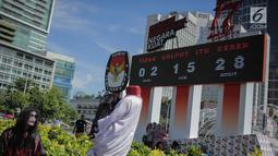 Warga berfoto di depan papan hitung mundur pelaksanaan Pemilu sebagai bagian dari sosialisasi di Bundara HI, Jakarta, Minggu (14/4). Papan tersebut dipasang bertujuan untuk mengingatkan sekaligus mengajak masyarakat untuk mengawasi proses demokrasi terbesar di Indonesia. (Liputan6.com/Faizal Fanani)