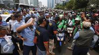Ratusan pengendara Go-Jek terlibat kericuhan dengan sopir taksi di Jakarta, Selasa (22/3). Ratusan Go-Jek mendatangi para sopir taksi karena tersebar isu pemukulan terhadap beberapa pengendara Go-Jek oleh sopir taksi.  (Liputan6.com/Immanuel Antonius)