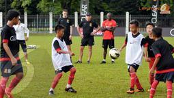 Dwight Yorke dan pelatih Manchester United Soccer Schools memperhatikan dengan serius anak-anak SSB Asiop Apacinti yang mengikuti Training Camp Ayo Indonesia Bisa (Liputan6.com/Helmi Fithriansyah)