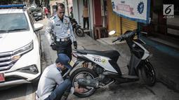 Petugas Dishub DKI Jakarta merazia  kendaraan roda dua dengan mencopot pentil yang terparkir di trotoar di kawasan Cipete Raya, Jakarta, Selasa (13/8/2019). Razia tersebut dilakukan Dishub untuk mengembalikan fungsi trotoar untuk pejalan kaki. (Liputan6.com/Faizal Fanani)