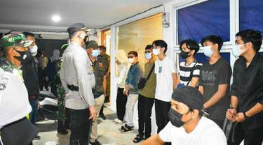 Petugas memberikan peringatan kepada warga yang masih berkerumun melewati jam malam.
