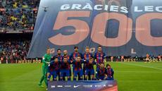 Pemain Barcelona berpose dengan latar belakang spanduk besar penghormatan untuk Lionel Messi yang telah mencetak 500 gol untuk klubnya sebelum pertandingan liga Spanyol antara Barcelona vs Osasuna di stadion Camp Nou, Barcelona (26/4). (AFP/Lluis Gene)