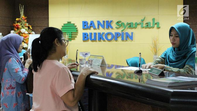 Nasabah melakukan transaksi di Bank Bukopin Syariah, Jakarta, Selasa (30/1). Data OJK yang terekam sampai Oktober 2017 mencatat, pertumbuhan aset perbankan syariah mencapai 19,79% secara tahunan menjadi Rp 395,89 triliun. (/Angga Yuniar)
