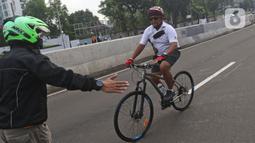 Petugas mengarahakan pesepeda non road bike saat memasuki JLNT Kampung Melayu-Tanah Abang, Jakarta, Minggu (30/5/2021). Uji coba kedua ini bertujuan kembali mendapatkan masukan dari penggiat sepeda secara lengkap baik dari sisi operasional maupun teknis kedepannya. (Liputan6.com/Herman Zakharia)