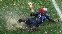 Pemain timnas Prancis, Benjamin Mendy memegang trofi Piala Dunia 2018 saat merayakan gelar juara setelah mengalahkan Kroasia pada  laga final di Luzhniki Stadium, Minggu (15/7). Prancis membekuk Kroasia dengan skor akhir 4-2. (AP Photo/Rebecca Blackwell)