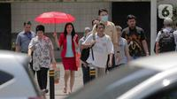 Seorang wanita menggunakan payung menyebrang selama gelombang panas di Jakarta, Selasa (22/10/2019).  BMKG memprediksi wilayah Indonesia akan mengalami panas selama kurang lebih satu minggu ini. Hal ini dikarenakan matahari yang berada dekat dengan jalur khatulistiwa. (Liputan6.com/Faizal Fanani)