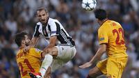 Pemain Juventus, Giorgio Chiellini, berebut bola dengan pemain Sevilla pada laga Liga Champions Grup H di Juventus Stadium, Turin, Kami (15/9/2016) dini hari WIB. (AFP/Marco Bertorello)