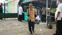 Warga berjalan usai pembagian daging kurban di sekitar Masjid Al Azhar, Jakarta, Jumat (1/9). Masjid Al Azhar Jakarta memotong dan mendistribusikan ratusan hewan kurban pada Hari Raya Idul Adha 1438 H. (Liputan6.com/Helmi Fithriansyah)