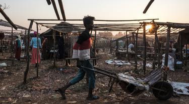 Seorang pemuda mendorong gerobak di antara kios-kios kosong pasar lokal di Kota Asosa, Ethiopia, Rabu (25/12/2019). (EDUARDO SOTERAS/AFP)