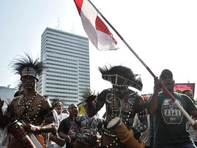 Masyarakat Papua yang merupakan mantan karyawan PT Freeport Indonesia saat melakukan penggalangan dana di tengah berlangsungnya Hari Bebas Kendaraan Bermotor atau Car Free Day di kawasan Bundaran HI, Jakarta, Minggu (5/8). (Merdeka.com/Iqbal S. Nugroho)