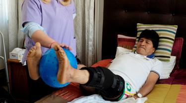 Presiden Bolivia, Evo Morales saat menjalani fisioterapi setelah operasi pada lutut kirinya di kediamannya di La Paz, Bolivia, (30/6). Evo Morales mengalami cedera ketika mengikuti pertandingan sepak bola pemerintahan. (REUTERS/David Mercado)