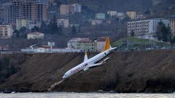 Pesawat maskapai Pegasus Airlines nyaris terperosok ke dalam laut saat mendarat di bandara Trabzon, Turki, Minggu (14/1). Pesawat itu tergeletak di tebing dengan bagian depannya hanya beberapa meter dari permukaan air Laut Hitam. (DHA-Depo Photos via AP)