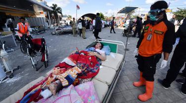 Korban gempa Lombok yang terluka menunggu bantuan medis di luar Rumah sakit Moh. Ruslan di Mataram, Senin (6/8). Aparat gabungan terus melakukan evakuasi dan penanganan darurat akibat bencana gempa bermagnitudo 7 yang mengguncang Lombok. (AFP/ADEK BERRY)