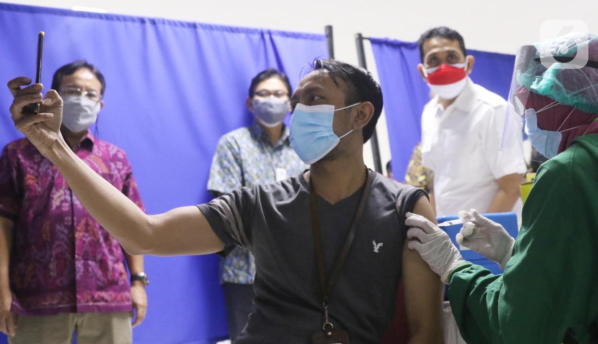 Warga mengabadikan momen saat vaksinasi covid-19 di sentra vaksin Tomang Tol Plaza, Tangerang, Sabtu (24/7/2021). Pemerintah sebelumnya menetapkan target sasaran vaksinasi 181,5 juta atau 70 persen dari total populasi untuk mencapai kekebalan kelompok atau herd immunity. (Liputan6.com/Angga Yuniar)