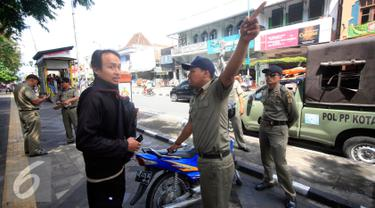 Petugas Satpol PP melakukan razia ke pengendara motor yang parkir di kawasan pendestrian Malioboro, Yogyakarta, (19/4). Petugas memberikan surat peringatan dan mengambil kartu identitasnya yang di tahan di KUPT Malioboro. (Liputan6.com/Boy Harjanto)
