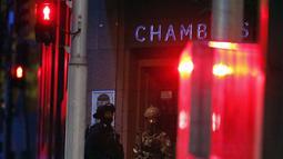 Polisi bersenjata lengkap berjaga di luar gedung yang berisi Kafe Lindt di Martin Place, Sydney (16/12/2014). Seorang pria bersenjata masuk ke Kafe Lindt dan menyandera beberapa orang yang berada di dalam kafe tersebut. (REUTERS/David Gray)