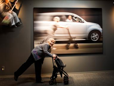 Seorang nenek bernama Kimiko Nishimoto berpose di depan karya foto-fotonya yang dipamerkan di Tokyo, Jepang (14/12). Kimiko Nishimoto adalah seorang nenek yang menjadi selebram dengan jumlah pengikut sebanyak 42 ribu. (AFP Photo/Behrouz Mehri)