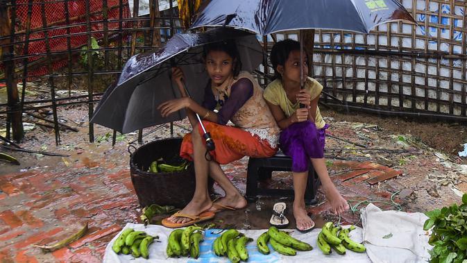 Dua anak perempuan pengungsi Rohingyah menjual pisang selama musim hujan di kamp pengungsi Kutupalong di Ukhia (12/9/2019). Kamp pengungsi Kutupalong dan Nayapara memiliki populasi sekitar 34.000 pengungsi yang terdaftar pada Juli 2017. (AFP Photo/Munir Uz Zaman)