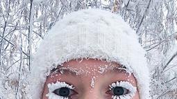 Anastasia Gruzdeva berswafoto dengan bulu mata yang membeku saat menerjang jalanan berselimut es di desa Oymyakon, Rusia, Minggu (14/1). Suhu di sana turun hingga -62 derajat Celcius yang cukup dingin untuk membekukan bulu mata (sakhalife.ru photo via AP)