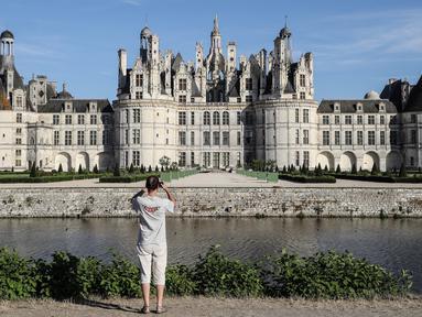 Seorang pengunjung mengambil gambar Kastil Chambord, di Chambord, Prancis pada 22 Juli 2020. Bangunan bersejarah ini merupakan salah satu kastil terbesar di Prancis sekaligus lokasi nyata yang menginspirasi film pertama Beauty and The Beast, 26 tahun lalu. (Photo by Ludovic MARIN / AFP)