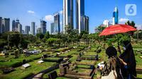 Warga melintas di antara makam di TPU Karet Bivak, Jakarta, Selasa (11/5/2021). Pemprov DKI akan memberlakukan larangan ziarah kubur Idulfitri di seluruh TPU mulai 12 hingga 16 Mei untuk mencegah terjadinya penyebaran Covid-19 saat berkumpul untuk berziarah. (Liputan6.com/JohanTallo)
