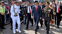 Presiden Joko Widodo didampingi Kapolri, Tito Karnavian beserta rombongan berjalan kaki menuju lokasi upacara HUT ke-72 TNI di Pelabuhan Indah Kiat, Banten (5/10). (Liputan6.com/Pool/Agus Suparto)
