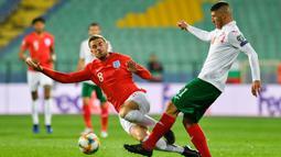 Bek Bulgaria, Kamen Hadzhiev, berusaha melewati gelandang Inggris, Jordan Henderson, pada laga Kualifikasi Piala Dunia 2020 di Stadion Vasil Levski, Sofia, Senin (14/10). Bulgaria kalah 0-6 dari Inggris. (AFP/Nikolay Dychinov)